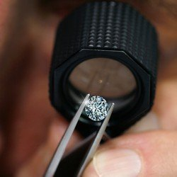observation of a diamond with a magnifying glass, held with pliers
