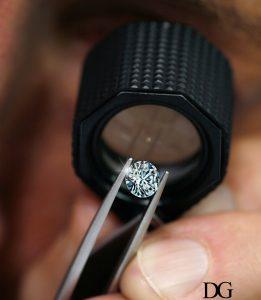 observation d'un diamant à la loupe, tenu par une pince