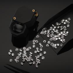 stocks of white diamonds with magnifying glass and pliers