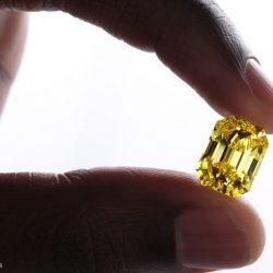 diamante giallo, taglio a smeraldo tenuto tra due dita