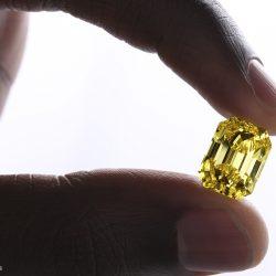 yellow diamond, emerald cut held between two fingers